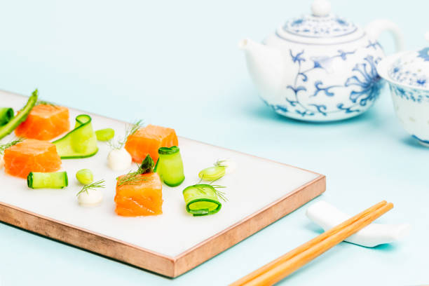Dices of raw salmon with asparagus, edamame beans, cream cheese and zucchini on a marble plate aside a Chinese teapot and some chopsticks on a blue background. Copy space. Side top view. stock photo