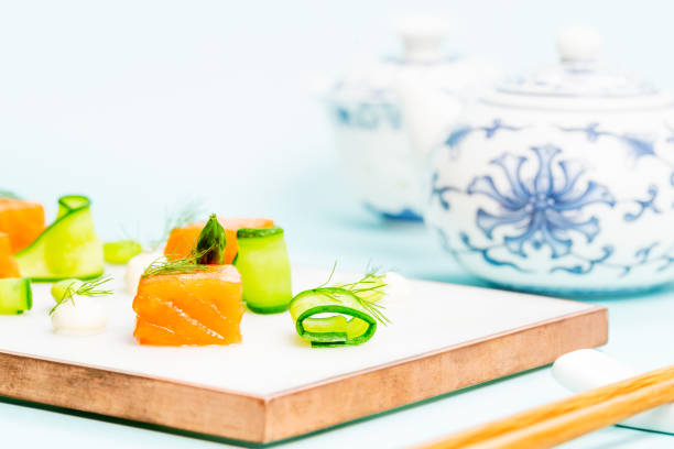 Dices of raw salmon with asparagus, edamame beans, cream cheese and zucchini on a marble plate aside a pair of chopstick and a Chinese tea pot over an infinite blue background with copy space. stock photo