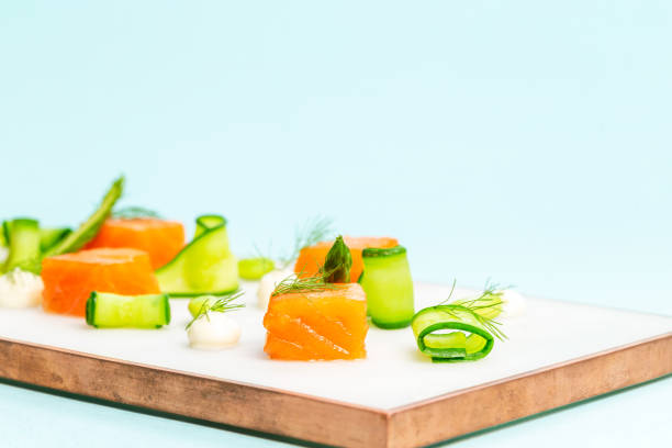 Dices of raw salmon with asparagus, edamame beans, cream cheese and zucchini on a marble plate over an infinite blue background. stock photo