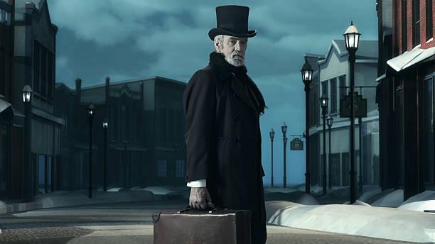 dickens scrooge mann in alten winter street ab. hält koffer. - charles dickens weihnachtsgeschichte stock-fotos und bilder