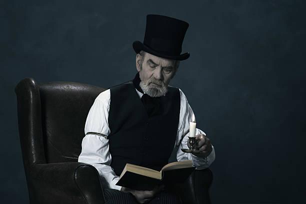 dickens scrooge mann sitzt im sessel, lesen buch bei kerzenschein. - charles dickens weihnachtsgeschichte stock-fotos und bilder