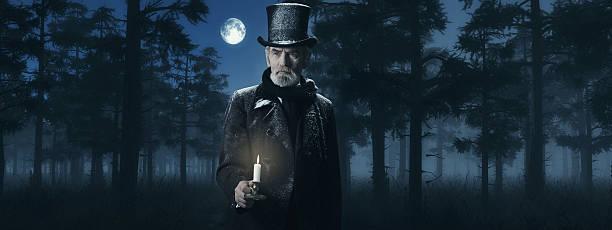 dickens scrooge mann mit candlestick in einem nebligen wald im winter. - charles dickens weihnachtsgeschichte stock-fotos und bilder