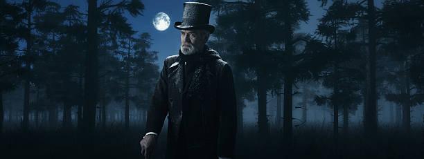 dickens scrooge mann mit spazierstock in misty winter forest. - charles dickens weihnachtsgeschichte stock-fotos und bilder