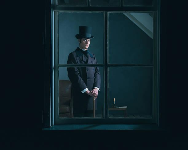 dickens style man standing with cane behind window. - charles dickens weihnachtsgeschichte stock-fotos und bilder