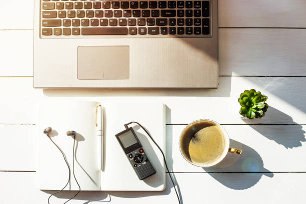dictaphone with headphones on a light worktable of a journalist with a notebook, a green succulent and a laptop. in the sunlight - dictaphone stock pictures, royalty-free photos & images
