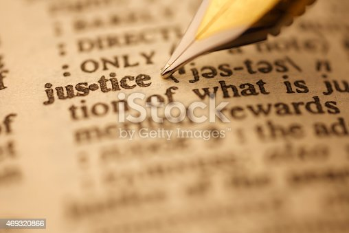 Justice pen nib pointing to the words in the dictionary, shot with very shallow depth of field,