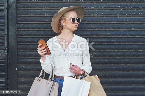 Cropped shot of an attractive young woman looking away thoughtfully while holding a smartphone and shopping bags against an urban background