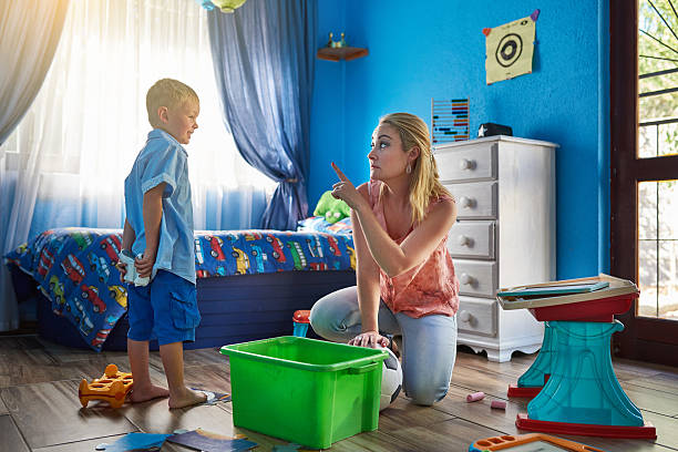 Did I not ask you to pack your toys away? Shot of a mother disciplining her son at home kids cleaning up toys stock pictures, royalty-free photos & images