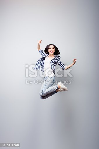 istock I did it! Dreams come true! Concept of freedom, happiness and life without problems. Vertical full length portrait of happy crazy woman is jumping up, isolated on grey background 927911768