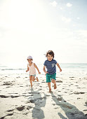 Portrait of two young siblings running on the beach