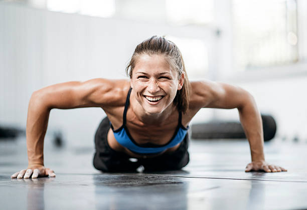 I did the last one! Young woman doing push ups at the gym and having fun tuff stock pictures, royalty-free photos & images