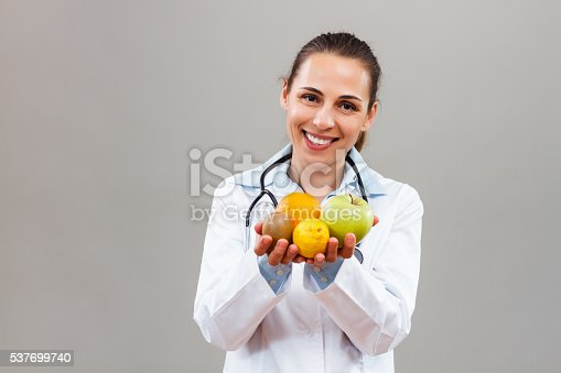 Beautiful female doctor is holding fruit to remind us how  is important to eat healthy.