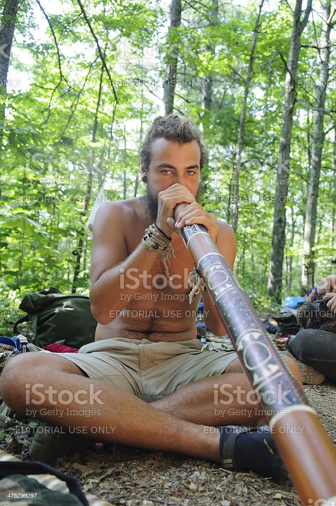 Didgeridoo in the forest at Rainbow Gathering royalty-free stock photo