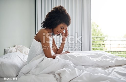 Shot of a young woman suffering from a headache while sitting in her bed
