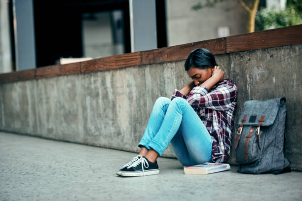 I didn't know it would be this hard Shot of a young female student sitting on the floor feeling depressed outside on campus apprehension stock pictures, royalty-free photos & images