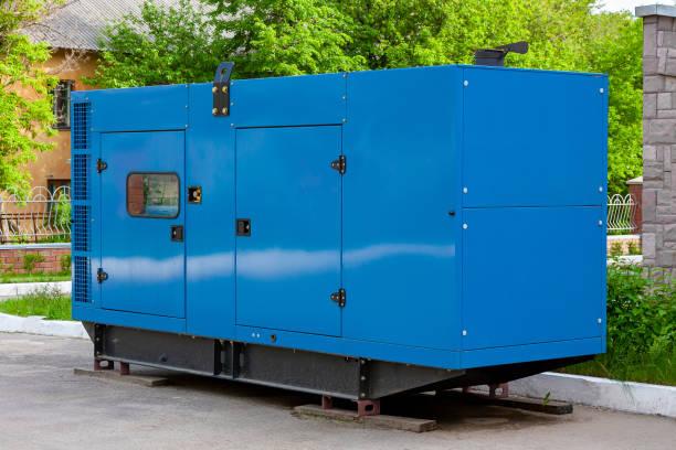 Dieselgenerator für die Notstromversorgung an der Wand eines medizinischen Zentrums vor dem Hintergrund grüner Bäume bei schönem Wetter. – Foto