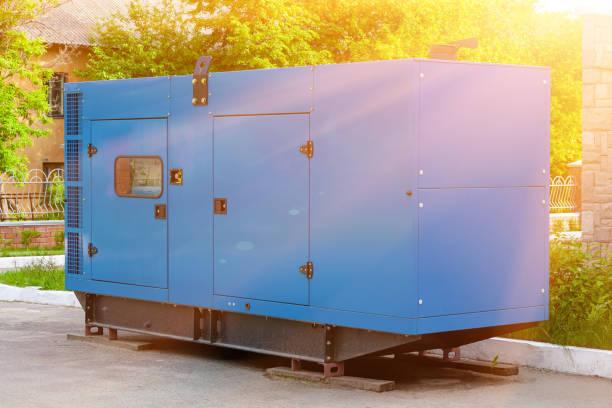Dieselgenerator für die Notstromversorgung an der Wand eines medizinischen Zentrums vor der Kulisse grüner Bäume bei schönem Sonnigem Wetter. – Foto