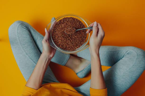 dieet en gewicht verlies thema op de oranje achtergrond. vrouw houdt boekweit in de plaat en lepel. vrouw op dieet. - boekweit stockfoto's en -beelden