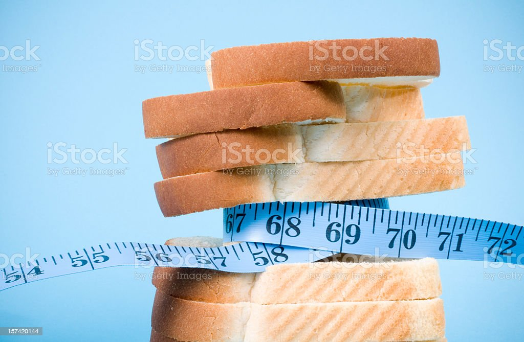 Diet breads and measure tape on blue background stock photo