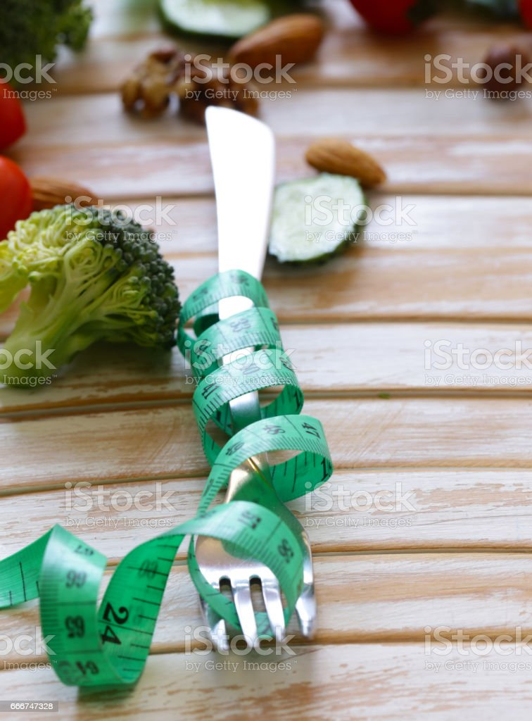 Diet concept - fork with measuring tape on a wooden table foto stock royalty-free