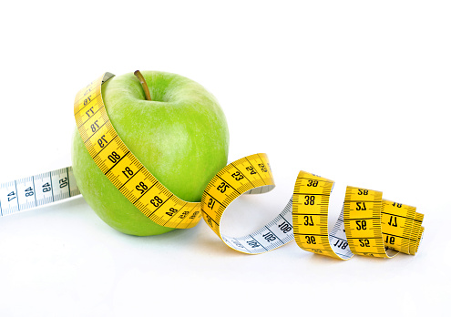 istock Diet concept, green apple wrapped with measuring tape 517971794