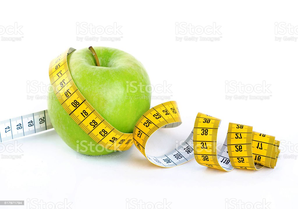 Diet concept, green apple wrapped with measuring tape stock photo