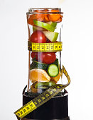 Conceptual image - fresh fruits and vegetables in a mixer with measuring tape on a white background.