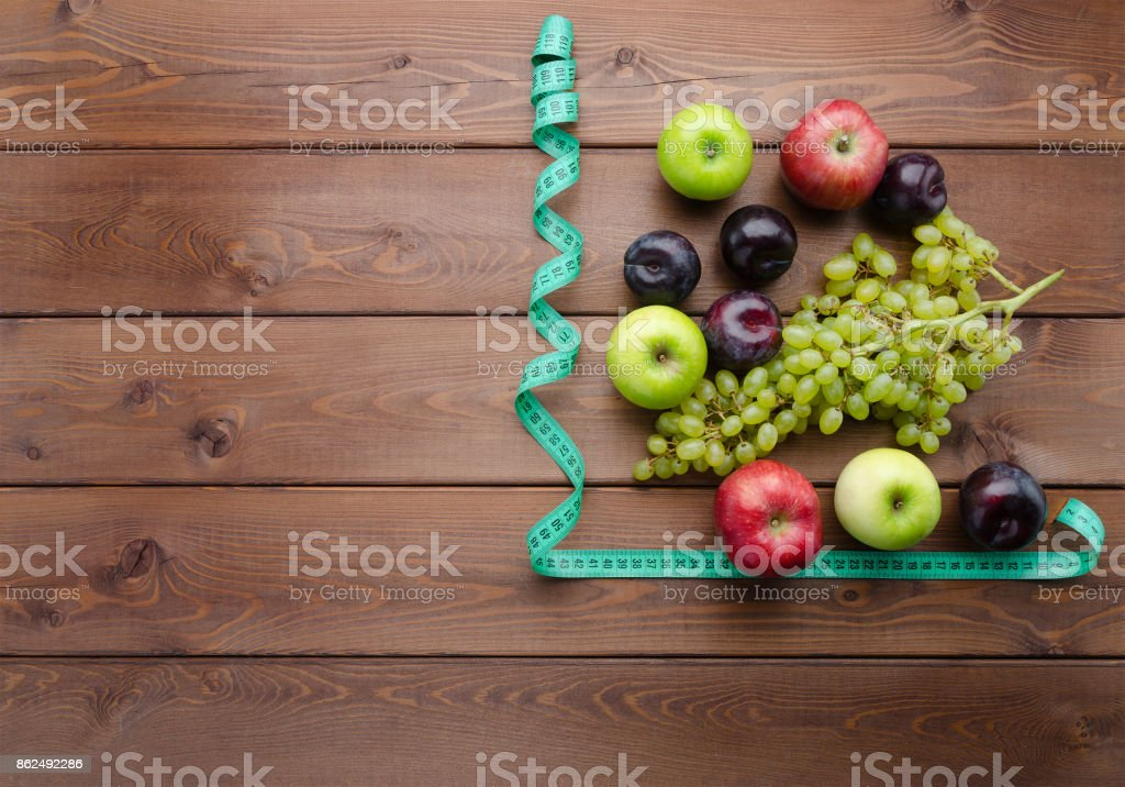 Diet concept with measuring tape and fresh fruits stock photo