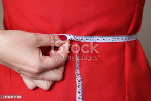 1163494373 istock photo Diet concept, woman in red dress with measuring tape around the waist 1126057299