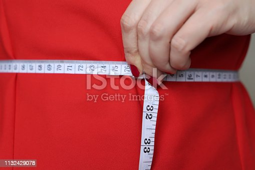 1163494373 istock photo Diet concept, woman in red dress with measuring tape around the waist 1132429078