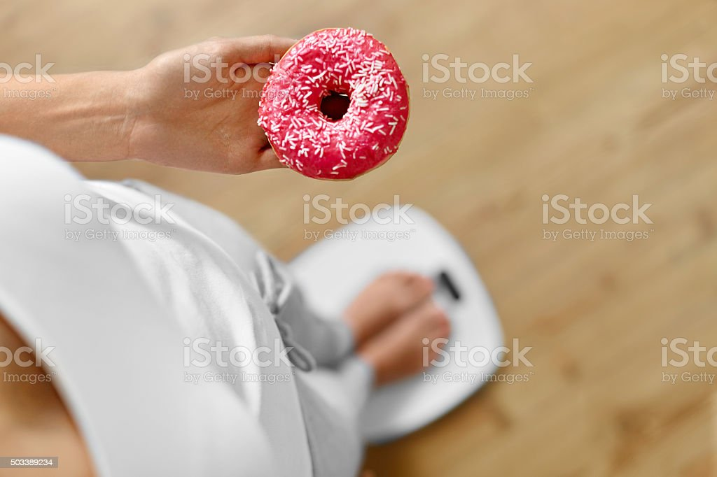 Diet Concept. Woman On Scale Holding Donut. Weight Loss. Dieting stock photo