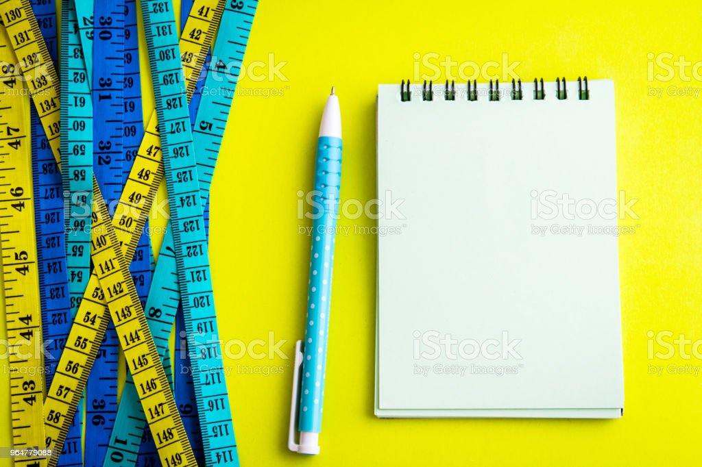 Diet control concept background. Colorful of Measuring tape on vibrant color  background with book diary notepad and  pen for healthy fitness  background. royalty-free stock photo