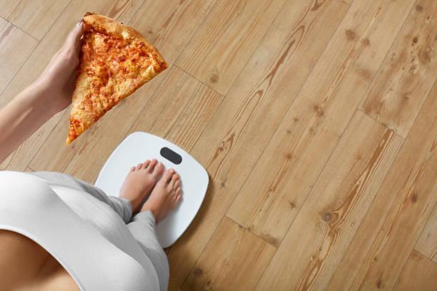 ernährung, fast food. frau auf waage halten pizza. adipositas. - gewicht schnell verlieren stock-fotos und bilder