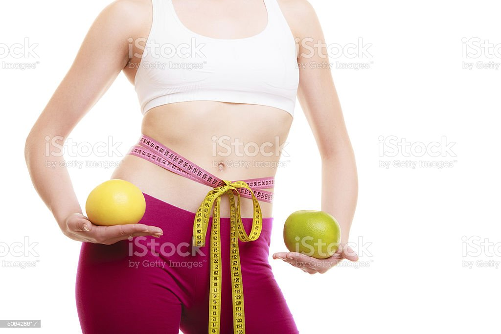 Diet. Fit girl with measure tapes citrus fruits stock photo