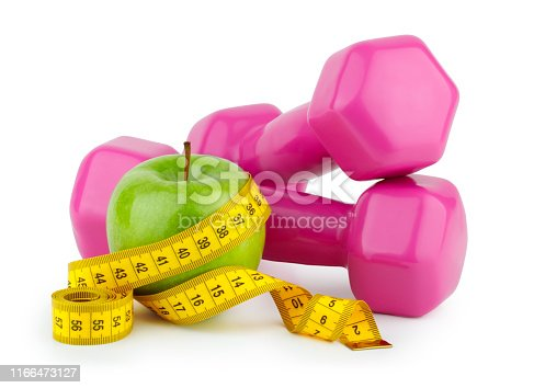 Diet, fitness and sport concept. Pink dumbbell, measuring tape and green apple on white background