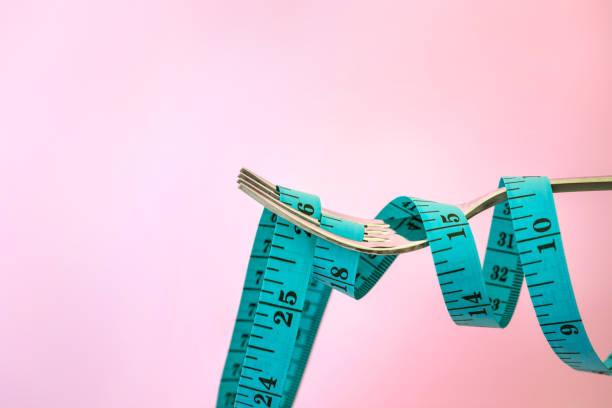 Diät zur Gewichtsabnahme, Maßband mit Gabel auf einem rosa Hintergrund für kümmern sich um gesunde Ernährung Konzept – Foto