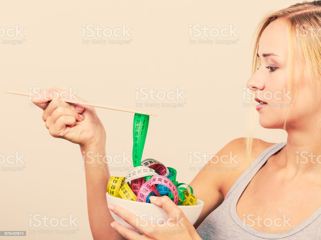 Diet. Girl with colorful measuring tapes in bowl royalty-free stock photo