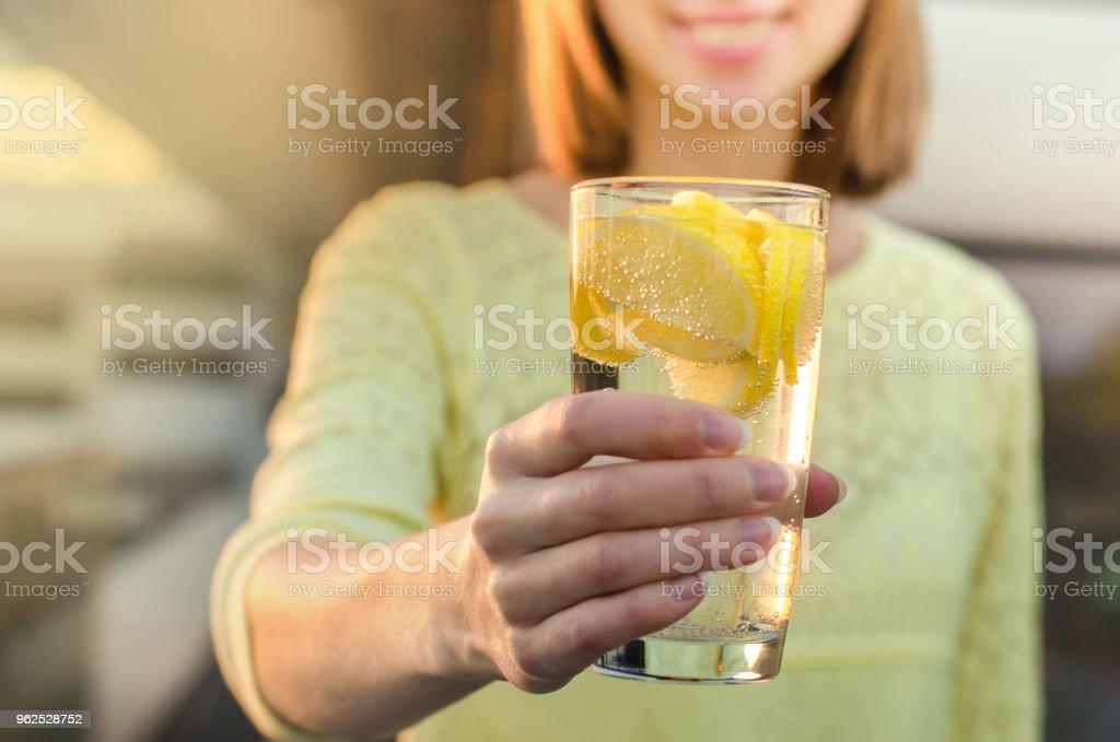 Dieta. Uma alimentação saudável. Mão de uma mulher segurando o copo de limonada no fundo borrado natureza ao ar livre. Sucos de vegetais frescos de desintoxicação. Estilo de vida saudável, comida vegetariana. Conceito de nutrição. - Foto de stock de Adulto royalty-free