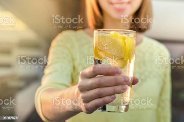Foto de Dieta Uma Alimentação Saudável Mão De Uma Mulher Segurando O Copo De Limonada No Fundo Borrado Natureza Ao Ar Livre Sucos De Vegetais Frescos De Desintoxicação Estilo De Vida Saudável Comida Vegetariana Conceito De Nutrição e mais fotos de stock de Adulto