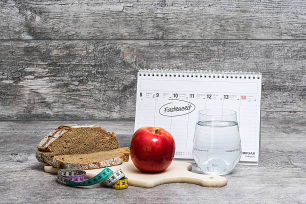 "Diet Meal Grey Background with Calendar (Fastenzeit) Diet meal on a grey background with calendar and the german word for Lent ""Fastenzeit"". lent stock pictures, royalty-free photos & images"