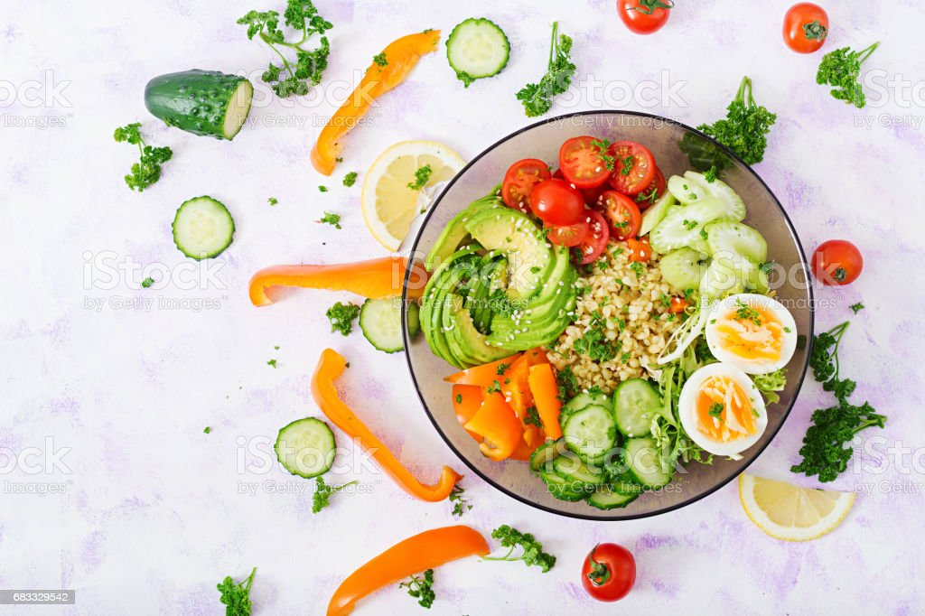 Diet menu. Healthy lifestyle. Bulgur porridge, egg and fresh vegetables - tomatoes, cucumber, celery and avocado on plate. royalty-free stock photo