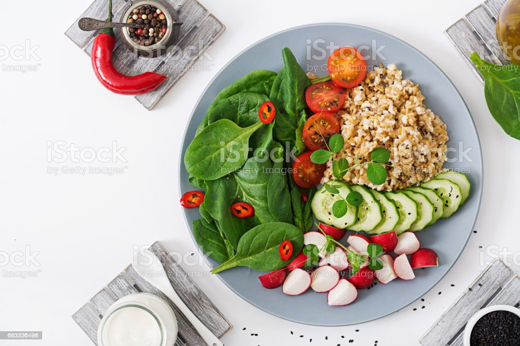 Diet menu. Healthy lifestyle. Vegan salad of fresh vegetables - tomatoes, cucumber, radish, spinach and oatmeal on bowl. Flat lay. Top view royalty-free stock photo