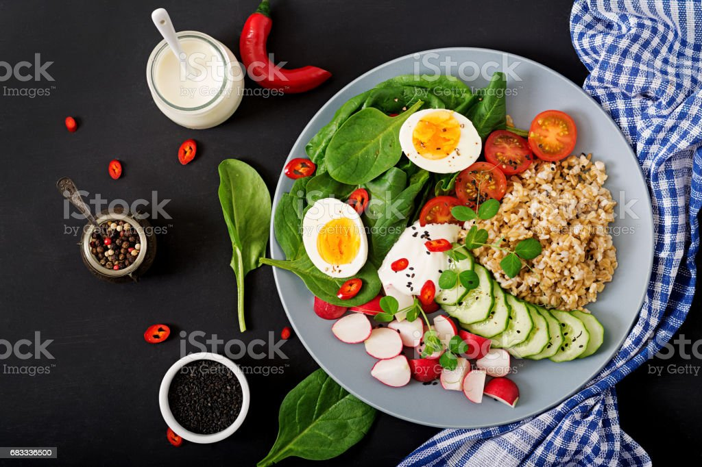 Diet menu. Healthy salad of fresh vegetables - tomatoes, cucumber, radish, egg, spinach and oatmeal on bowl. Flat lay. Top view royalty-free stock photo