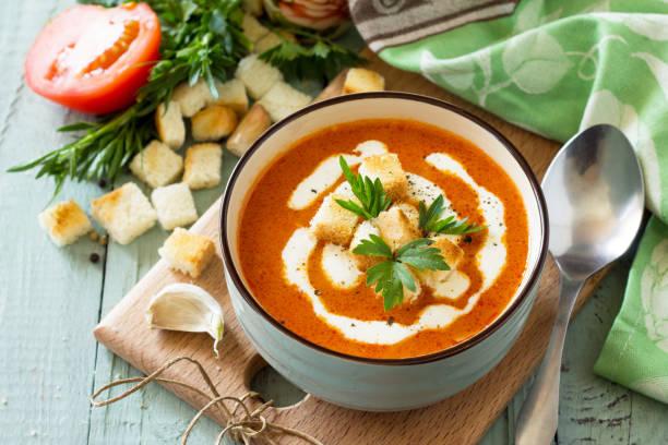 diät-menü. pürieren sie tomaten suppe mit croutons und sahne in einer schüssel auf einem küchentisch aus holz. das konzept einer gesunden ernährung. - hausgemachte tomatensuppen stock-fotos und bilder