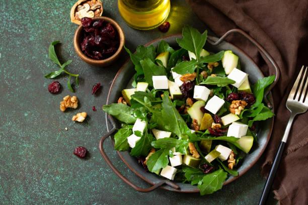 다이어트 메뉴, 비건 음식. 아루굴라, 페타 치즈, 배, 견과류, 말린 크랜베리, 비네그레트 소스를 얹은 건강한 샐러드.  텍스트에 사용할 수 있는 여유 공간입니다. 스톡 사진