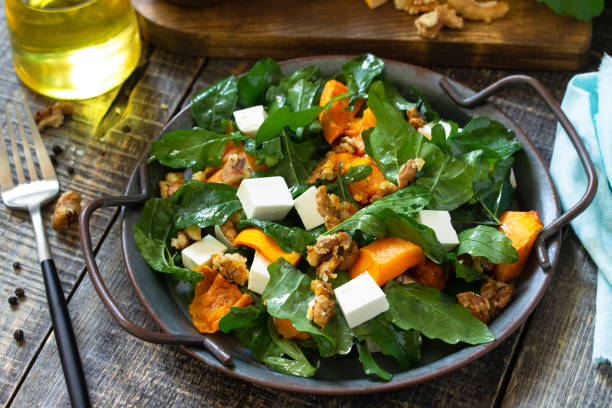 다이어트 메뉴, 비건 음식. 구운 호박, 페타, 치즈, 비네그레트 드레싱을 소박한 나무 테이블에 얹은 건강한 샐러드. 스톡 사진