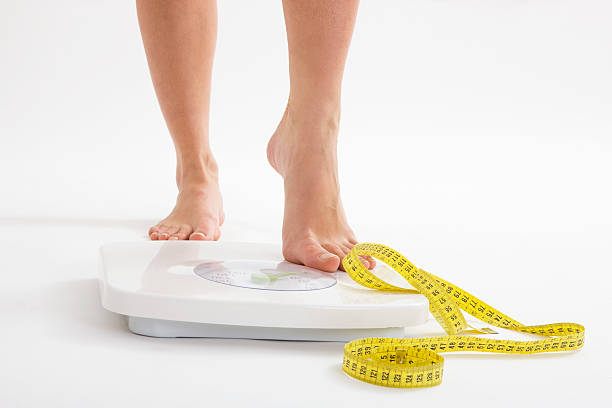 Diet Woman stepping on scale, canon 1Ds mark III stepping stock pictures, royalty-free photos & images