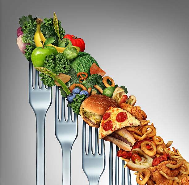 Diet Relapse Diet relapse change as a healthy lifestyle slowly goes downward to greasy unhealthy fast food concept as a dieting quality decline symbol of returning to bad eating habits as a group of descending forks with meal items on them. devolve stock pictures, royalty-free photos & images
