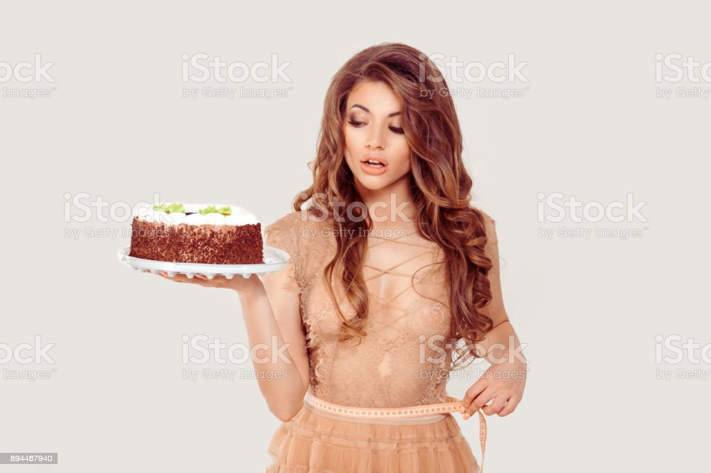 Diet. The happy middle age beautiful woman holding looking at cake craving for sugar holding measure tape on waist on white. Girl with full makeup curly brown long hair blue eyes nude color lace dress stock photo