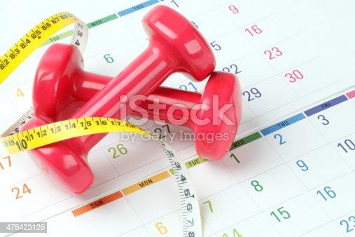 Tape measure and dumbbell on calendar